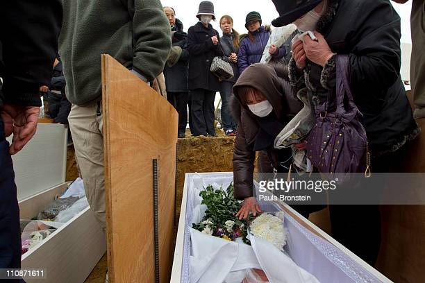 Relatives of the dead place flowers on the body as they identify their family members at a temporary burial ground on March 25 2011 in...