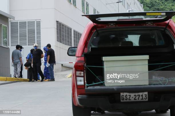 Relatives of the diseased wait outside the Guasmo Sur Hospital to recover their remains as a car transports a casket on April 4 2020 in Guayaquil...