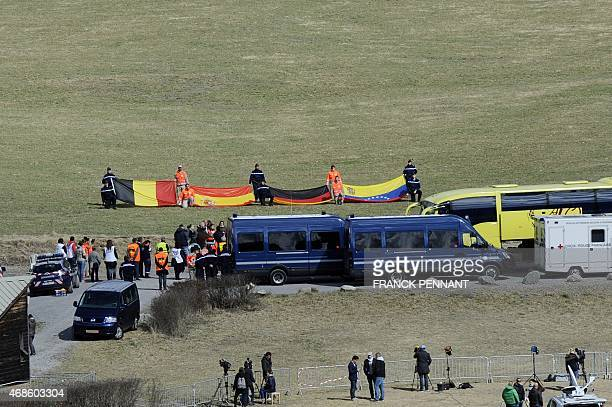 Relatives of the Germanwings Airbus A320 crash victims arrive on April 4 2015 to attend a ceremony as rescuers hold flags of the late passengers'...