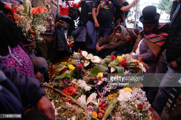 Relatives of the men killed during clashes with police at the Senkata fuel plant lay out flowers during a funeral ceremony on November 21 2019 in El...