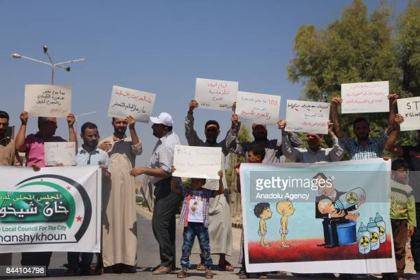 Relatives of the people who were killed on Assad regime forces' chemical gas attack on April 4 hold placards as they gather to protest after Friday...
