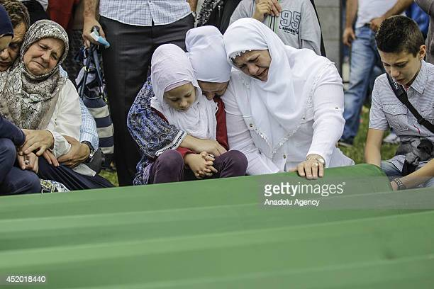 Relatives of the Srebrenica victims mourn and pray in tears near the coffins at SrebrenicaPotocari Memorial and Cemetery during the mass burial...