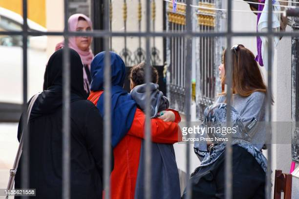 Relatives of the victim are seen with one of the sons of the couple outside the door of a residence where a civil guard officer killed himself after...