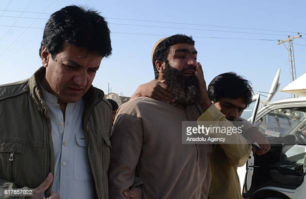 Relatives of the victims cry outside the Balochistan Police Training College in Quetta on October 24 after militants attacked the training college At...