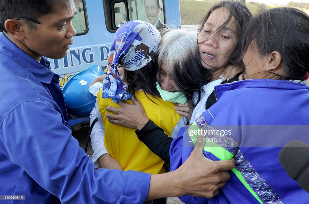 Relatives of the victims of an industrial accident at a power plant in Manila, grieve after identifying the bodies on February 4, 2013. Five workers were killed and dozen injured when a scaffolding collapsed while they were repairing a smokestack, according to rescuers. AFP PHOTO / Jay DIRECTO