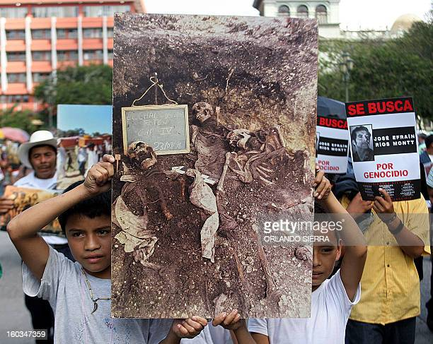 Relatives of the victims of the 19601996 civil war show a picture of a mass grave during a protest rally against former Guatemalan dictator Efrain...