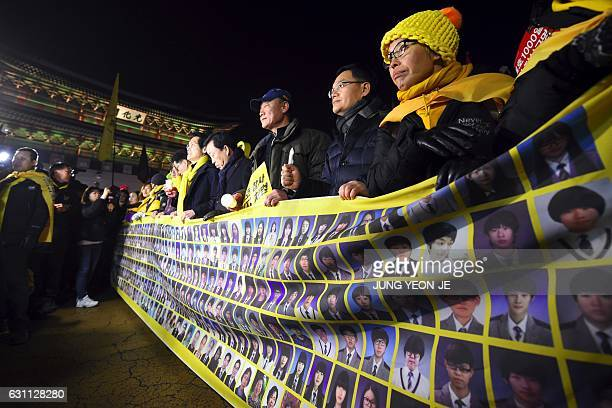 Relatives of the victims of the 2014 Sewol ferry disaster carry a banner showing portraits of the victims during a protest demanding impeached South...