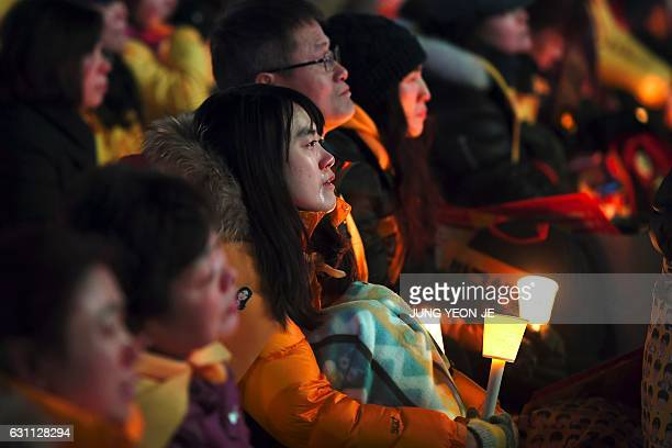 TOPSHOT A relatives of the victims of the 2014 Sewol ferry disaster cries during a protest demanding impeached South Korea's President Park GeunHye...