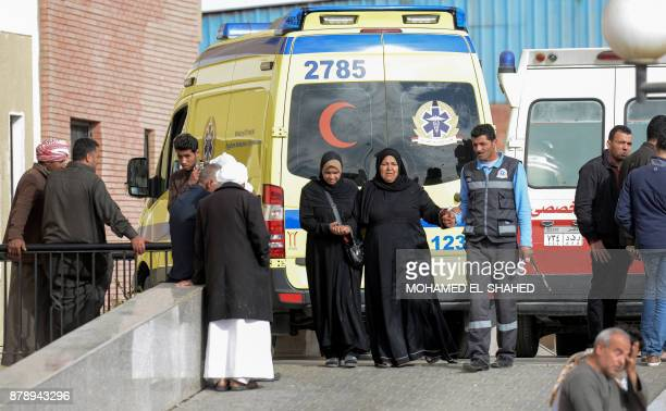 Relatives of the victims of the bomb and gun assault on the North Sinai Rawda mosque walk past an ambulance while waiting outside the Suez Canal...