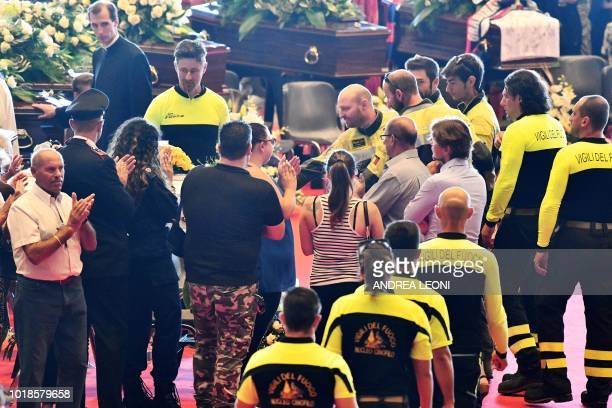 TOPSHOT Relatives of the victims of the collapsed Morandi highway bridge applaud Italian firefighters as they arrive to pay their respects at the...