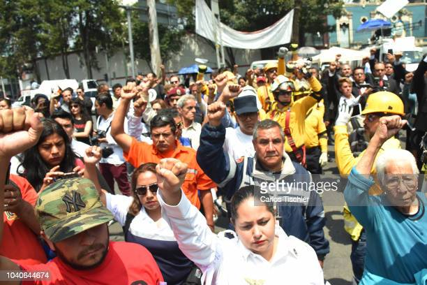 Relatives of the victims of the earthquake raise their fists during the minute of silence offered for people who died in the earthquake at 286 Alvaro...