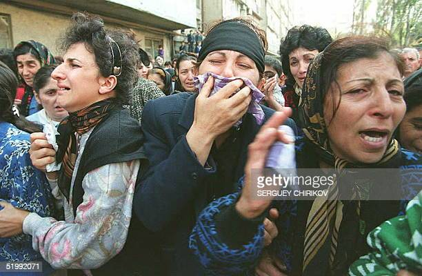 Relatives of the victims of the fire in the Baku, Azerbaijan, metro cry during a massive burial ceremony in Baku 30 October. Some 300 people died and...