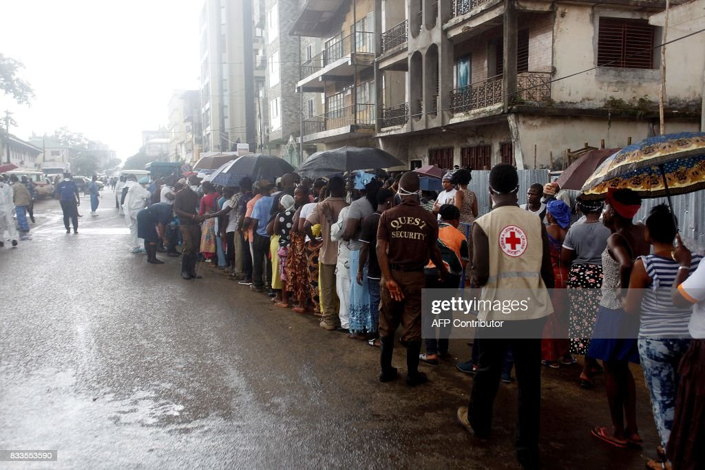 Relatives of the victims of the mudslide queue outside an hospital in Freetown on August 16, 2017. The first mass burials of victims of Sierra Leone's devastating floods and mudslides take place on August 17, as blame grows over government 'inaction' over deforestation and poor urban planning. / AFP PHOTO / Mohamed Saidu BAH