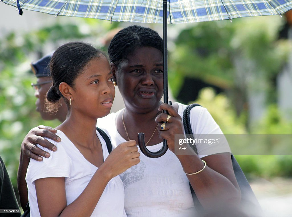 Relatives of the victims of the plane crash cry as they watch rescue workers download the remains of their beloved, upon arrival at the Zorg en Hoop airport in Paramaribo on May 17, 2010. Eight people, including pilot and co-pilot, died in a plane crash on May 15 in the hinterlands of Suriname. This is the third accident, second with casualties, with an Antonov airplane of Blue Wing airline in two years in Surinam.
