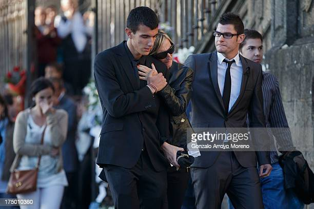 Relatives of the victims of the Spanish train crash pass flowers messages and candles placed on the steps in front of Santiago de Compostela...