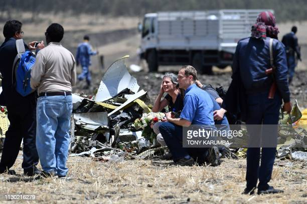 Relatives of the victims of the Sunday plane crash take a picture next to a pile of airplane fuselage at the crash site of the Ethiopian Airlines...