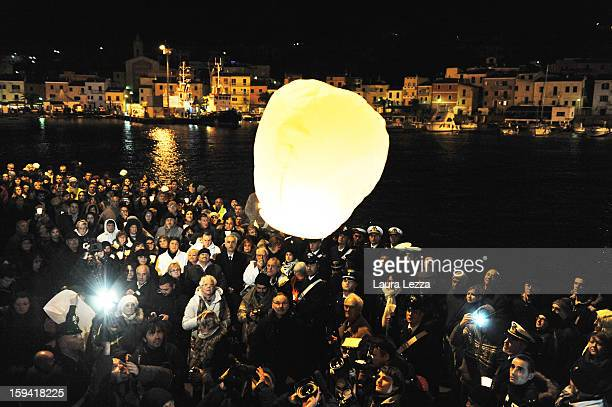 Relatives of the victims of the sunken Costa Concordia release a lantern into the sky after a minute of silence to mark the exact time the ship...