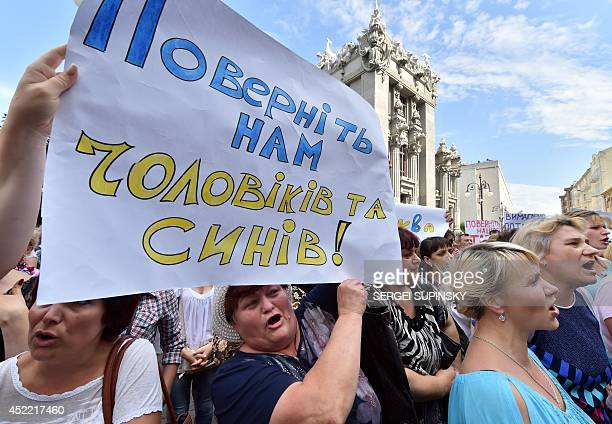 Relatives of Ukrainian servicemen who fight proRussian militants in the east of the country shout slogans as they hold placard reading Bring back our...