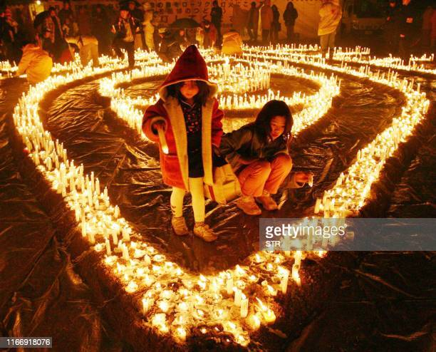 Relatives of victims and volunteers light some 6000 candles for the candlelight memorial service for the 1995 Hanshin earthquake victims at a park in...