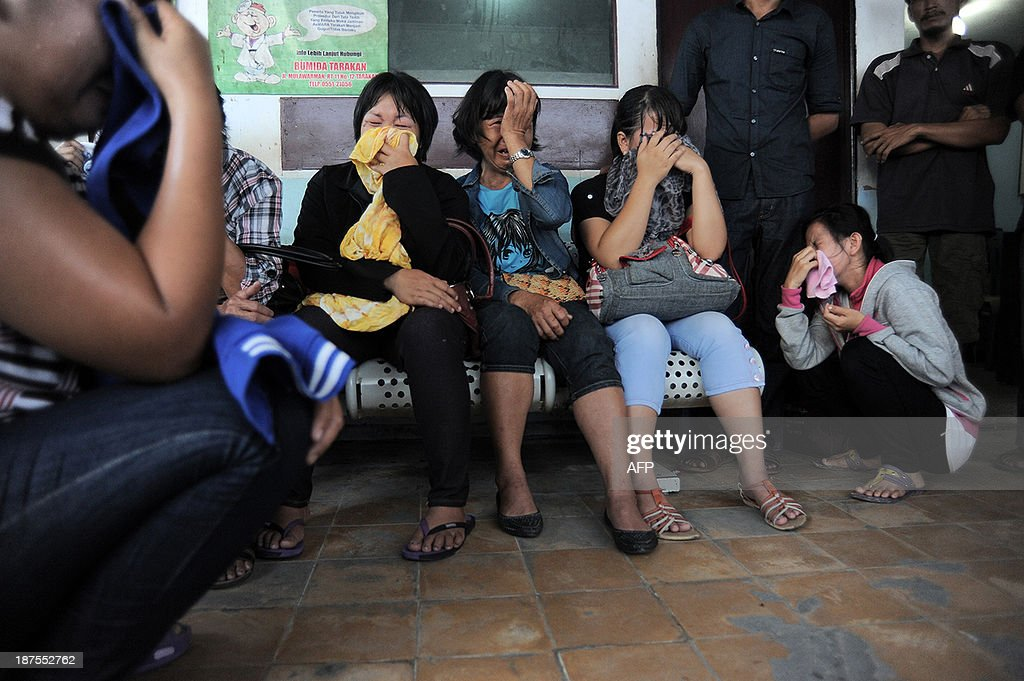 Relatives of victims cry as an Indonesian search and rescue team carry out the evacuation at Tarakan military airport in Tarakan on November 10, 2013. Thirteen people died when an Indonesian army helicopter carrying construction workers to build a military outpost crashed in the jungles of Borneo on November 9 and burst into flames, an official said.