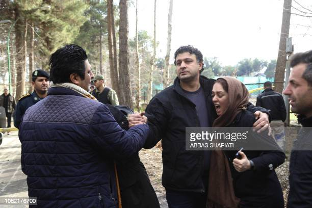 Relatives of victims mourn as they gather near the debris of a Boeing 707 cargo plane that reportedly crashed into a residential complex near the...
