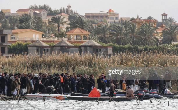 Relatives of victims of a capsized boat gather along the shore of Lake Mariout, 20 kilometres west of Egypt's second city of Alexandria on February...