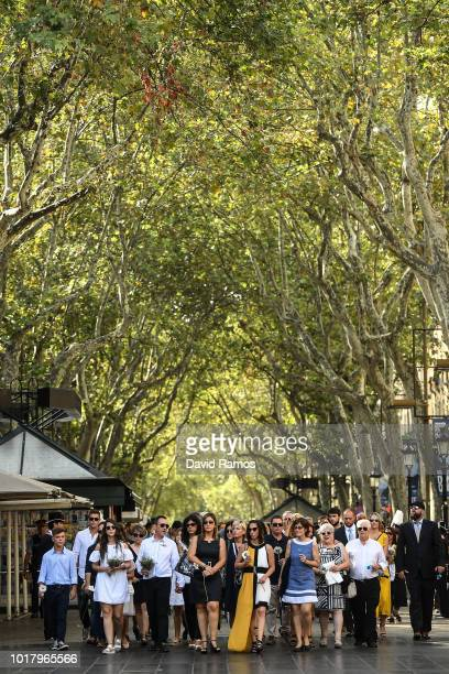 Relatives of victims of Barcelona and Cambrils terror attacks walk down Las Ramblas boulevard before laying a floral tribute at Las Ramblas on August...
