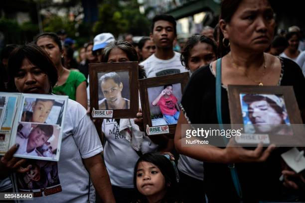 Relatives of victims of extrajudicial killings carry pictures of their loved ones during a protest in Quezon city Metro Manila Philippines November 5...
