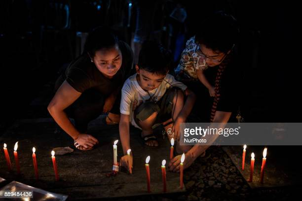 Relatives of victims of extrajudicial killings light candles next to pictures of their loved ones during a vigil in Quezon city Metro Manila...