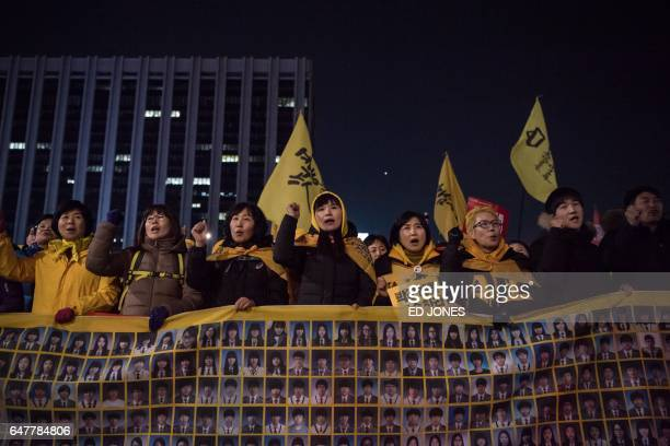 Relatives of victims of the 2014 Sewol ferry disaster join antigovernment activists during a rally in Seoul on March 4 2017 Tens of thousands of...