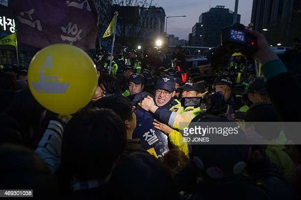 Relatives of victims of the Sewol ferry disaster scuffle with police as they attempt to march to the presidential Blue House in Seoul on April 11...