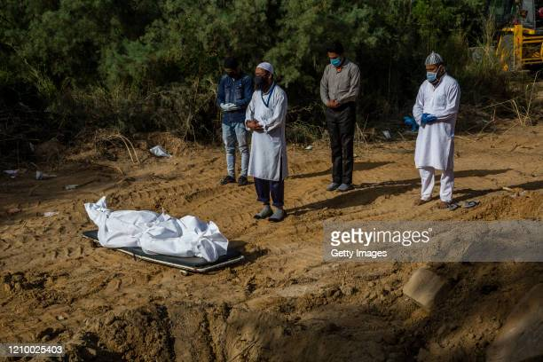 Relatives offer funeral prayers next to the body of a man who died from the coronavirus disease , before he is buried at a graveyard, as India...