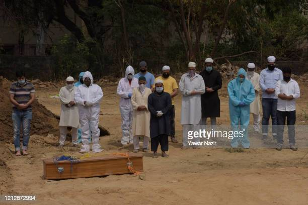 Relatives offer funeral prayers next to the coffin containing the body of a 23 years old man who died from the coronavirus disease , at a graveyard,...