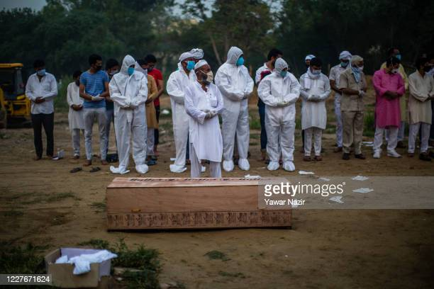 Relatives offer funeral prayers next to the coffin containing the body of a 35 years old Muslim man who died from the coronavirus disease , before...