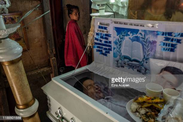 A relatives passes by the coffin of John Ryan Marquez on July 13 2019 in Malabon Metro Manila Philippines According to police Marquez was killed in a...