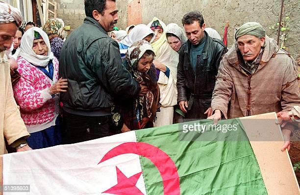 Relatives pay their last respects 17 December 1999 to one of the 16 December 1999 massacre victim in front of his house in the hamlet of Lampar 17...