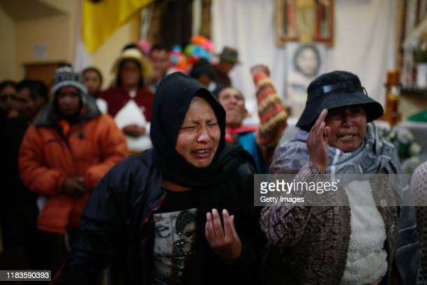 Relatives pray and cry during clashes between supporters of Evo Morales and security forces in the entrance of a major fuel plant at San Antonio de...