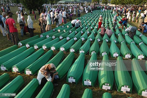 Relatives pray and mourn at the graves of 613 coffins of victims of the 1995 Srebrenica massacre laid out on a lawn at the Potocari cemetery and...