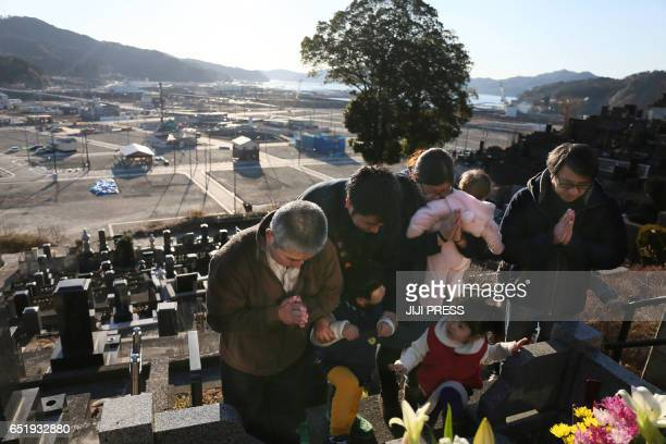 TOPSHOT Relatives pray while visiting their family's grave at the town of Otsuchi Iwate prefecture on March 11 2017 Japan is marking on March 11 the...