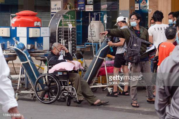Relatives seen outside Bekasi Public Hospital with their COVID-19 patients. Hospitals in Java, Indonesia are shifting medical emergency units to...