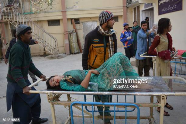 TOPSHOT Relatives shift an injured victim after suicide bombers attacked a Methodist church during a Sunday service in Quetta on December 17 2017 At...