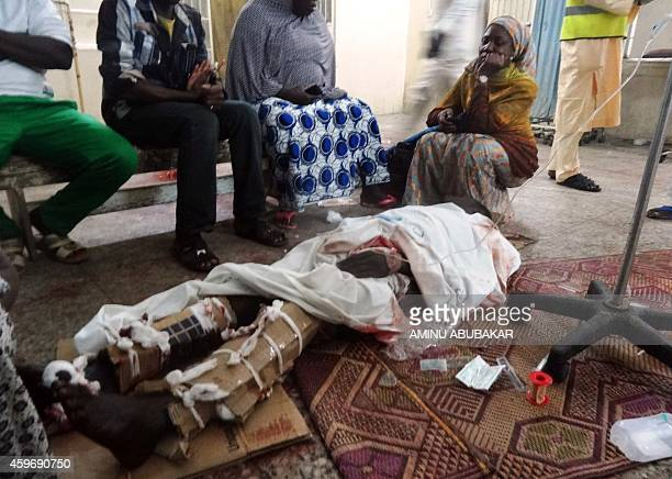 Relatives sit around one of the victims of twin suicide blasts at Kano central mosque in the accident and emergency ward of the Nassarawa Specilist...