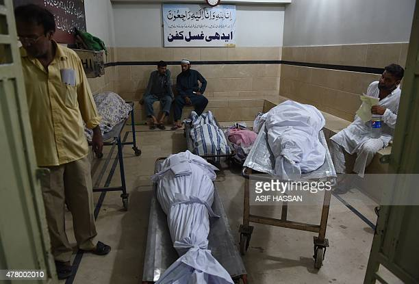 Relatives sit next to the dead bodies of heatwave victims at the EDHI morgue in Karachi on June 21 2015 A heatwave has killed at least 45 people in...