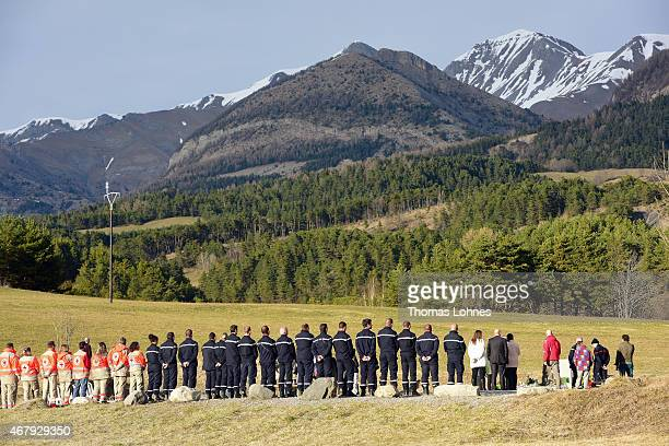 Relatives stand at a monument to honour the victims of Germanwings flight 4U9525 in front of the mountains near the crash site on March 26 2015 in Le...