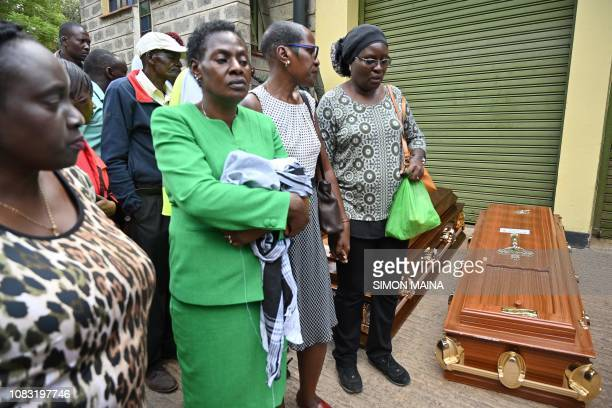 Relatives stand next to empty coffins at the Chiromo mortuary in Nairobi Kenya on January 16 2019 after a blast followed by a gun battle that rocked...