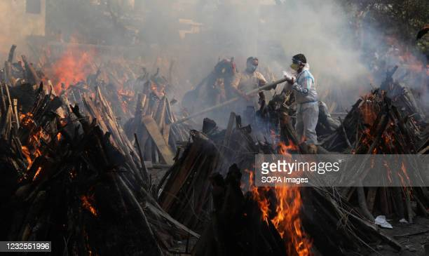 Relatives stand next to the burning funeral pyres of those who died due to the coronavirus disease , at Ghazipur cremation ground in New Delhi. In...
