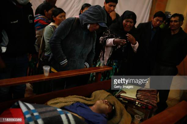 Relatives stand next to the coffins during the funeral of people killed yesterday during clashes between supporters of Evo Morales and security...