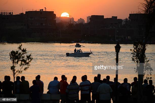Relatives stand on the bank of the Nile on July 23 north of the Egyptian capital Cairo as rescuers search for victims after at least 18 people...