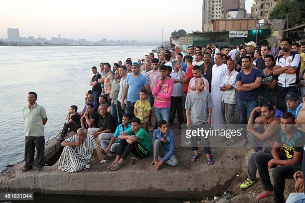 Relatives stand on the bank of the Nile on July 23 north of the Egyptian capital Cairo after at least 21 people celebrating an engagement were killed...