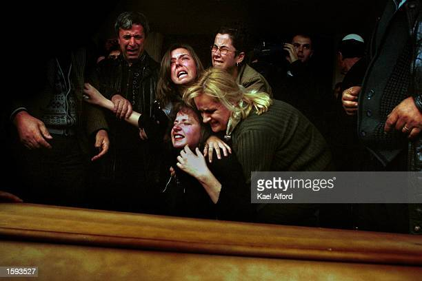 Relatives support Xhemajl Mustafa's daughter as she cries at her father's coffin November 24 2000 in the northern Kosovo village of Glamnik...